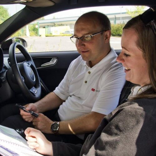 Driving pupil going through her learner driver guide with her instructor.