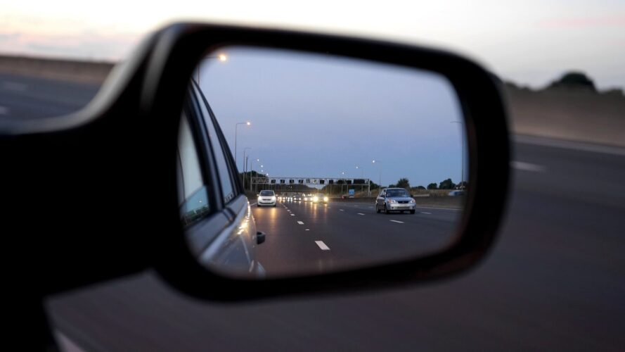 A car door mirror showing lanes of traffic behind. Learn to use these as part of the MSPSL routine.