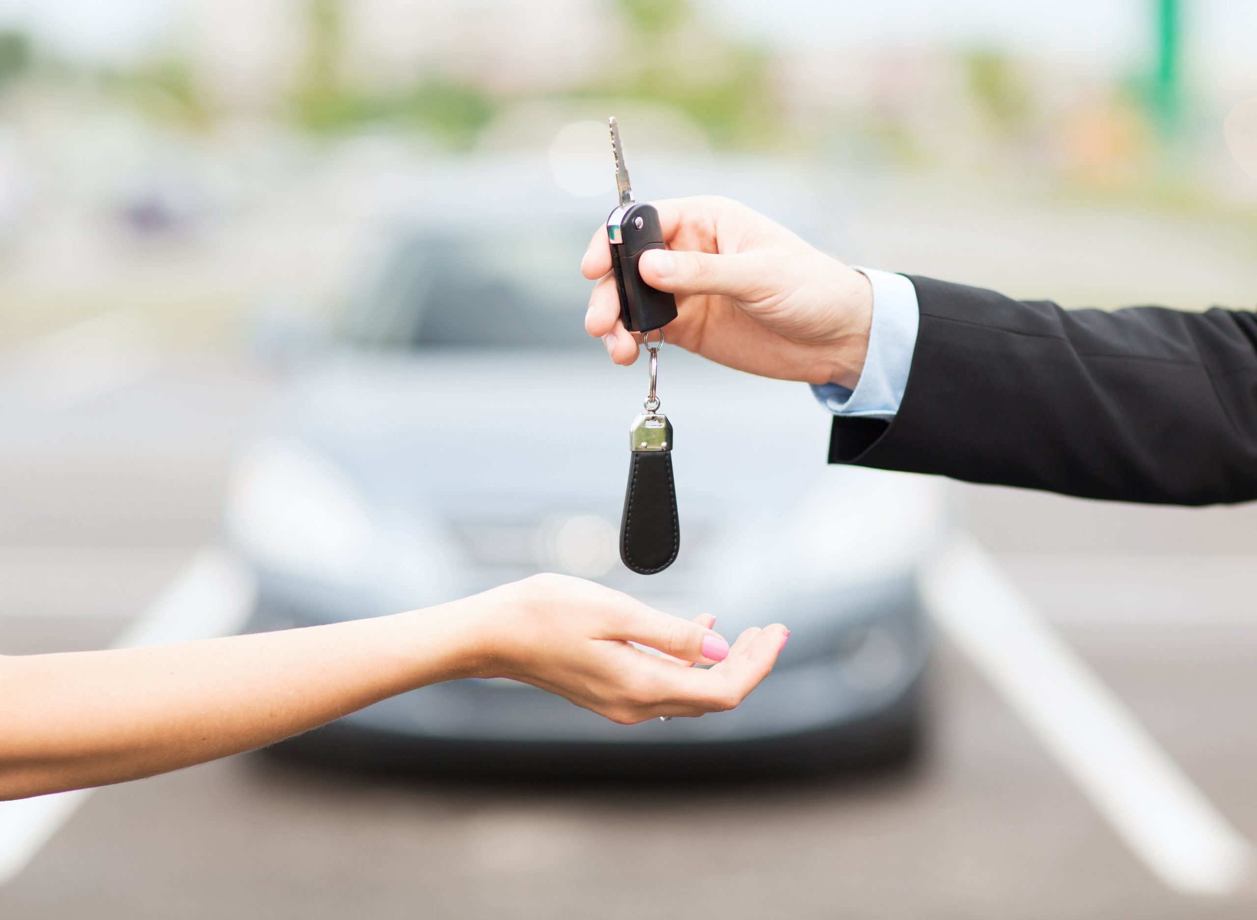 Picture of a car key being handed over to new owner